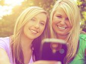 foto of two women taking cell phone  - two friends taking a selfie in a park while the sun is setting - JPG