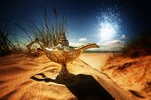 picture of aladdin  - Magic lamp in the desert from the story of Aladdin with Genie appearing in blue smoke concept for wishing - JPG
