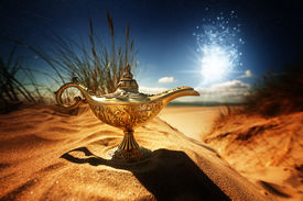 image of pantomime  - Magic lamp in the desert from the story of Aladdin with Genie appearing in blue smoke concept for wishing - JPG