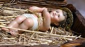 stock photo of manger  - Statue of baby Jesus in the Manger of the crib at Christmas - JPG