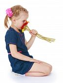 stock photo of little girls photo-models  - Girl in a blue short dress sniffing a bouquet of flowers - JPG