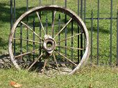 image of wagon wheel  - Photo of an old metal wagon wheel leaning against a fence - JPG