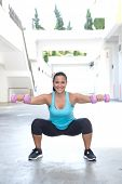 stock photo of squatting  - Beautiful hispanic sport woman doing squats with two pink dumbbell - JPG