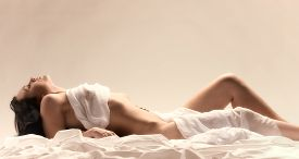 foto of curvy  - Attractive seminude woman wearing white fabric and she lying on the white bed sheets  - JPG