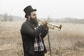picture of gypsy  - Stylish bearded gypsy plays trumpet on a wilderness path - JPG