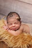 picture of sleeping  - Sleeping eight day old newborn baby girl with puckered lips. She is sleeping on gold faux fur and wearing a pearl and feather headband.