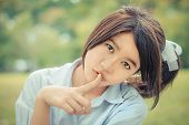 stock photo of hush  - Cute Thai schoolgirl doing hush gesture in green bokeh background in child color - JPG