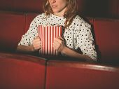 stock photo of watching movie  - A young woman is watching a suspense movie at the cinema and is clutching her popcorn - JPG