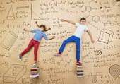 foto of frot  - Cute boy and girl learning playfully in frot of a big blackboard - JPG