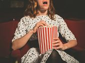 foto of watching movie  - A young woman is sitting on the front row in a movie theater and is watching an exciting film while eating popcorn - JPG