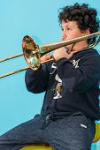pic of trombone  - child is exercised by the trombone with dedication concentration commitment - JPG