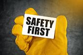 stock photo of precaution  - Safety First on Business Card Male Hand in Yellow Leather Construction Working Protective Gloves Holding Card with Rounded Corners - JPG