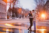 image of rainy season  - Portrait of young beautiful couple kissing in an autumn rainy day - JPG