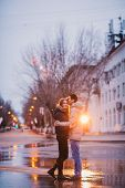stock photo of rainy day  - Portrait of young beautiful couple kissing in an autumn rainy day - JPG