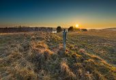 foto of barbed wire fence  - Early spring meadow with barbed wire fence at sunset - JPG