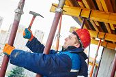 stock photo of millwright  - construction worker installing equipment for concrete work at building site - JPG