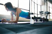 stock photo of yoga mat  - Young fit woman working out on yoga mat at gym - JPG