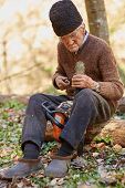 foto of man chainsaw  - Old farmer doing maintenance work to his chainsaw - JPG