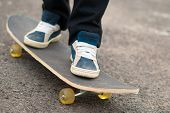 stock photo of skateboarding  - Skateboarder feet in sneakers on a skateboard - JPG