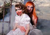 foto of zombie  - Zombie woman with fiery hair holding a baby in her arms zombie  - JPG