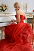 picture of evening gown  - Woman dressed in a red evening gown with a long train sits and playing on a white piano looking slightly to the side against a light background - JPG