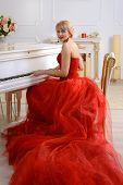 stock photo of evening gown  - Female dressed in a red evening gown with a long train sits and plays on a white grand piano looking slightly to the side against a light background - JPG