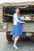 stock photo of  jeep  - Caucasian woman standing against back of military jeep - JPG