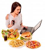 stock photo of high calorie foods  - Woman eating fast food at work - JPG
