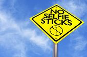 foto of wispy  - A yellow sign warns against taking selfies with a blue sky and wispy clouds - JPG