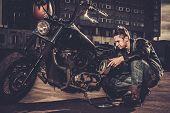 stock photo of carburetor  - Biker repairing his custom motorcycle bobber on a road  - JPG