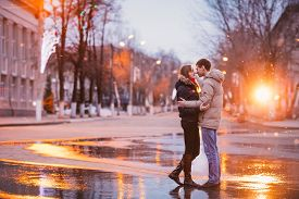 pic of rainy season  - Portrait of young beautiful couple kissing in an autumn rainy day - JPG
