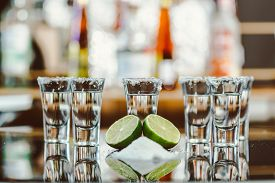picture of salt shaker  - two shots of tequila with lime and salt on a wooden table bar on the background of bright lights of the bar  - JPG