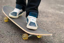 stock photo of skateboard  - Skateboarder feet in sneakers on a skateboard - JPG