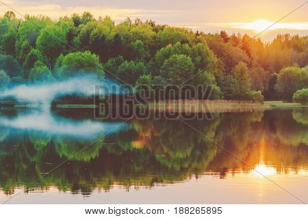 poster of A calm sunset on the shore of the lake where the forest reflects in calm water with haze and fog.