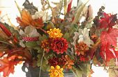 foto of flower arrangement  - A horizontal arrangement of flowers and fall colored leaves set in an antique coffee pot - JPG