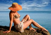 stock photo of beach hat  - The woman in a hat against the sea - JPG