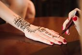 Master Mehndi Draws Henna On A Female Hand. poster