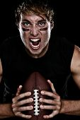 American football player screaming aggressive holding american football on black background. Strong  poster