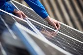 Male Engineer In Blue Suit Installing Solar Photovoltaic Panel System. Close Up View Of Electrician  poster