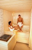 Young couple wearing towel talking in sauna, relaxing.?