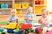 Nursery Babies Girl And Boys Playing Together In Playroom In Kindergarten poster
