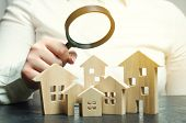 A Woman Is Holding A Magnifying Glass Over A Wooden Houses. Real Estate Appraiser. Property Valuatio poster