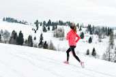 Young Woman Running On Snow In Winter Mountains Wearing Warm Clothing Gloves In Snowy Weather poster