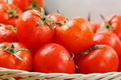 Small Red Tomatoes In A Wicker Basket On An Old Wooden Table. Ripe And Juicy Cherry poster