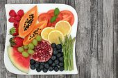 Health food for dieting and weight loss with fresh vegetables and fruit on a square plate on rustic  poster