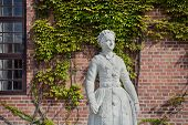 Danish Woman Statue In Traditional Costume. Street In Copenhagen With Artwork And Historical Houses, poster