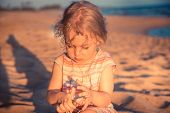 Beautiful Curious Child Girl Toddler Playing On Beach With Hermit Crab During Summer Vacation Concep poster