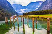 Wonderful trip on the lake tourist boat. The lake is surrounded by high mountains. Konigssee - the c poster
