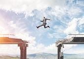 Businessman Jumping Over Huge Gap In Concrete Bridge As Symbol Of Overcoming Challenges. Skyscape An poster