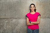 Smiling sporty young woman take a break after running. Confident latin girl leaning against wall in  poster